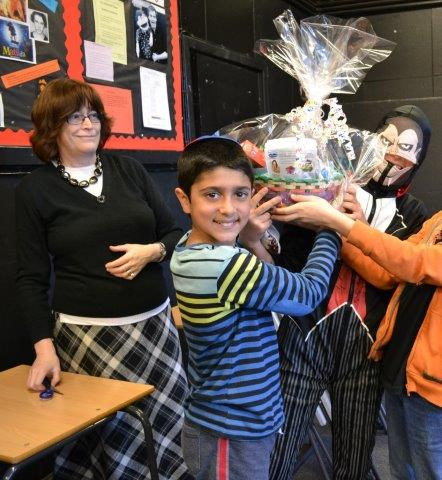 A Cheder pupil making a Purim basket (Mishloach Manot) to be presented to a member of the community with a teacher looking on